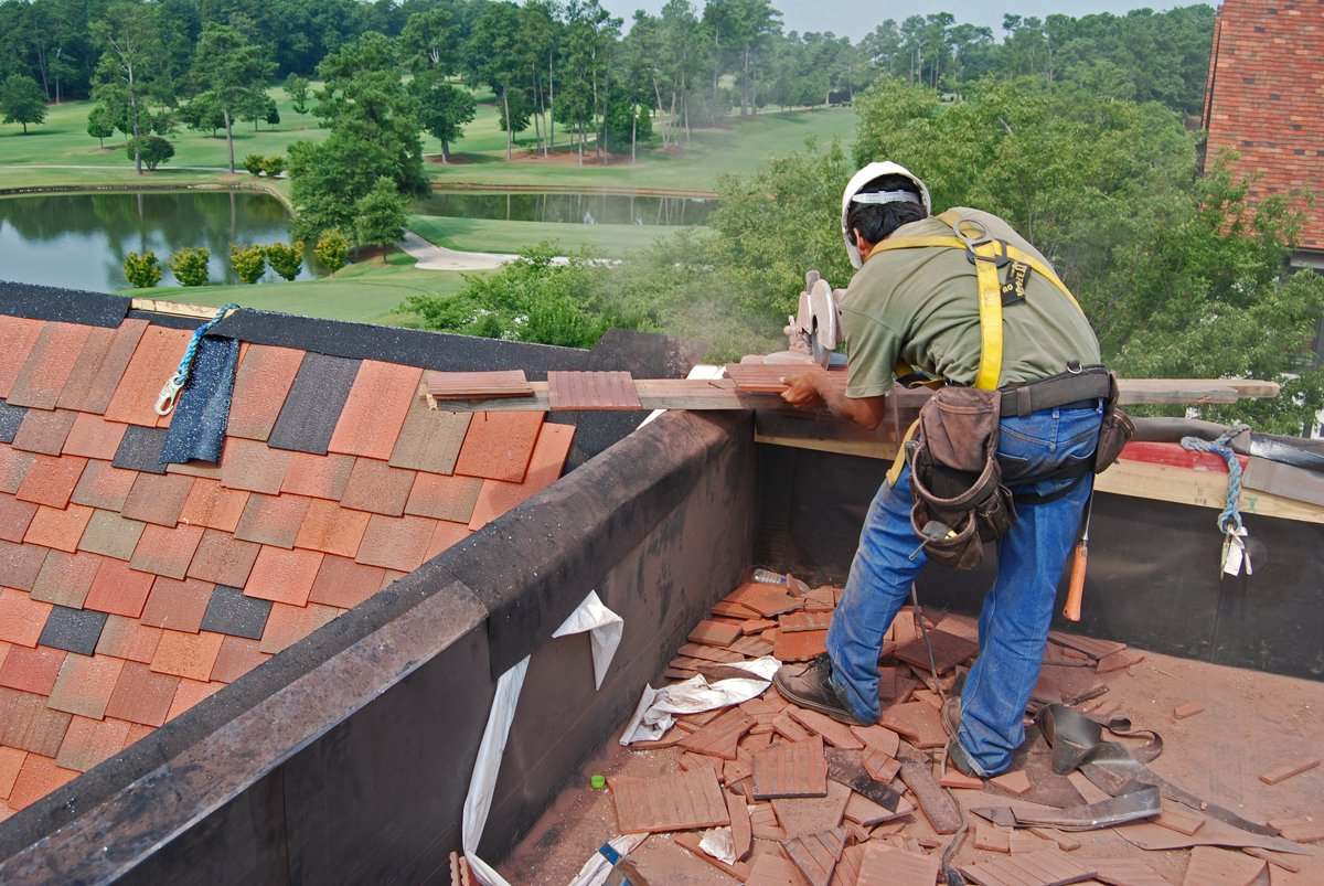 Roofing specialist replacing roof tiles