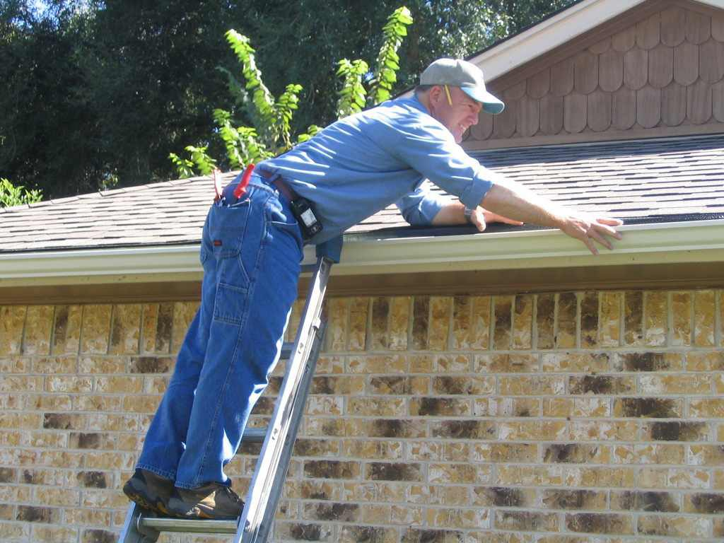 Roof with gutter getting repaired by a professional roofer